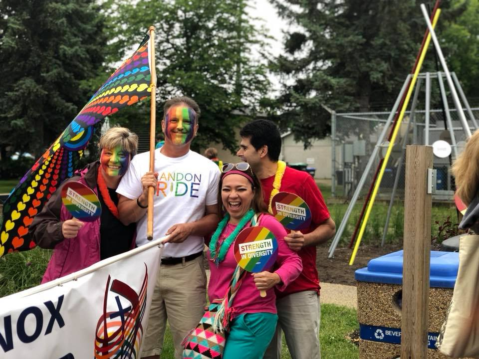 "A group of people with rainbow painted faces laughing and standing around a banner saying ""Knox United Church""."