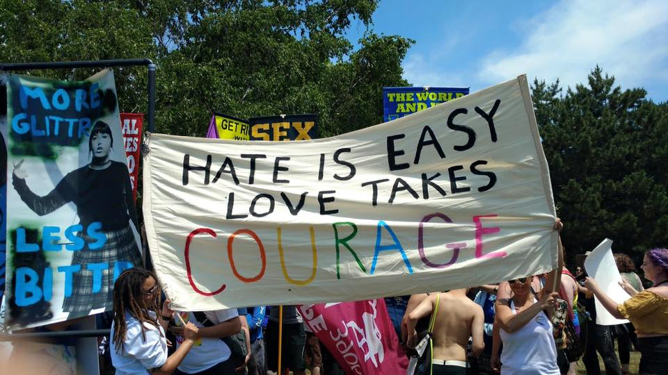 "A big cloth banner held by two people, blocking hateful signs behind. It says: Hate is easy, love take courage. ""Courage"" is in rainbow letters."