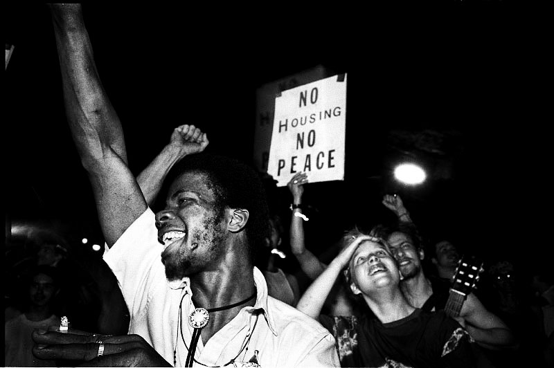 """black and white photo of people with fists in the air with a sign that reads """"no housing no peace"""""""