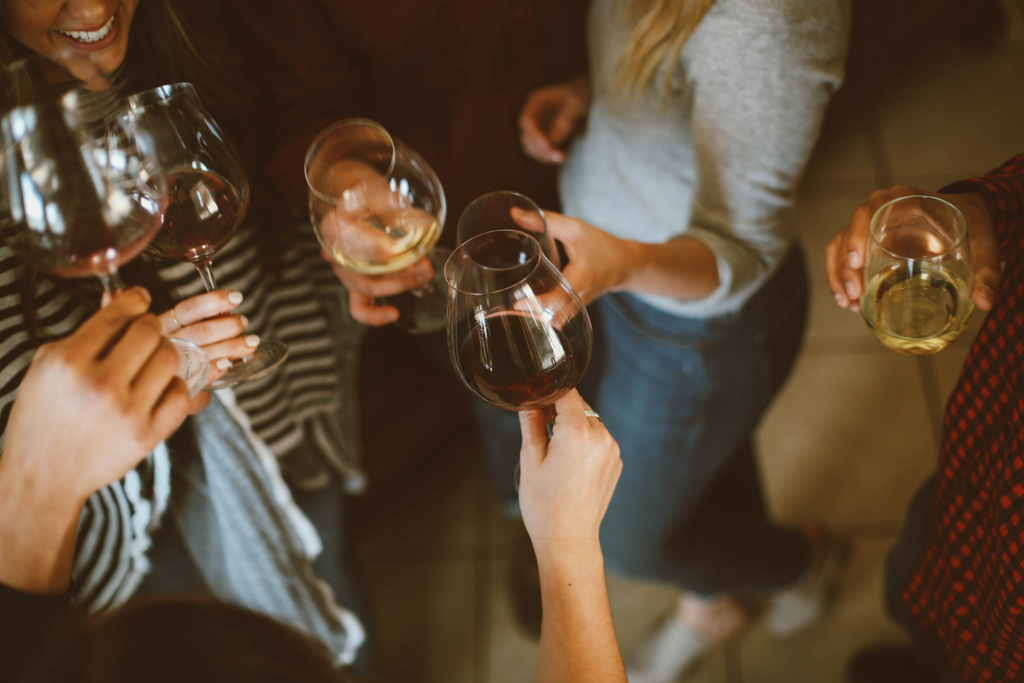 Grupo de pessoas a brindar com vinho branco e tinto