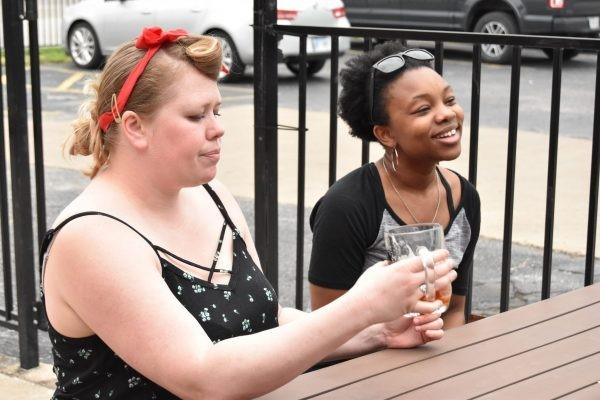Friends enjoy craft beer at patio table at Big Rip