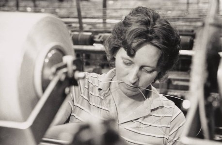 A woman works with threads in her mouth at Burlington Industries, date unknown.