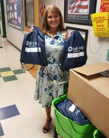 Teacher at a local school holds up backpacks donated by Self-Help Credit Union.