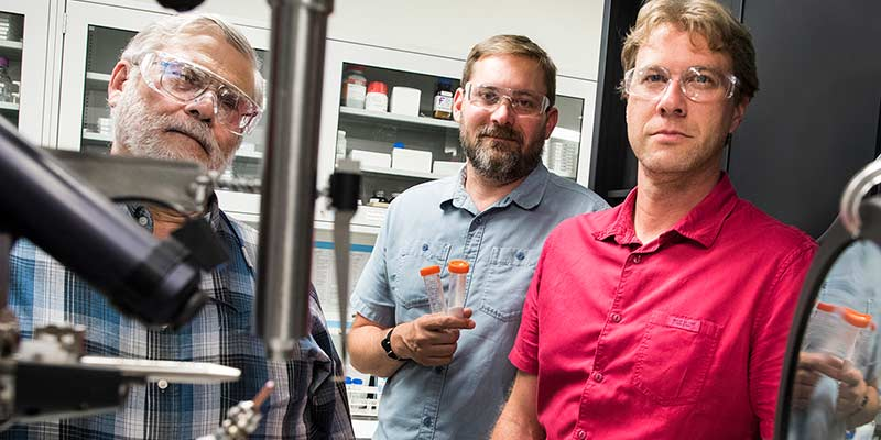 Three men stand near scientific equipment in a laboratory at NREL.