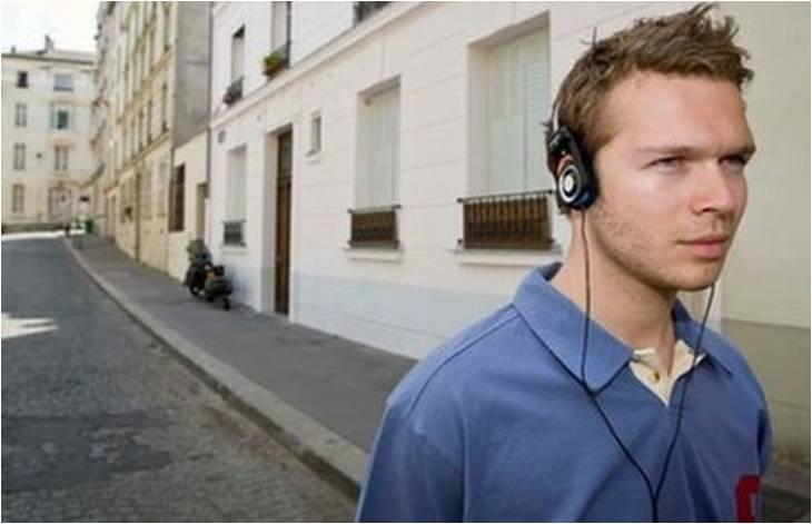 image of young man wearing earphones in street