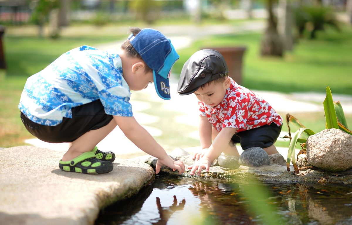 Two male children playing in pond