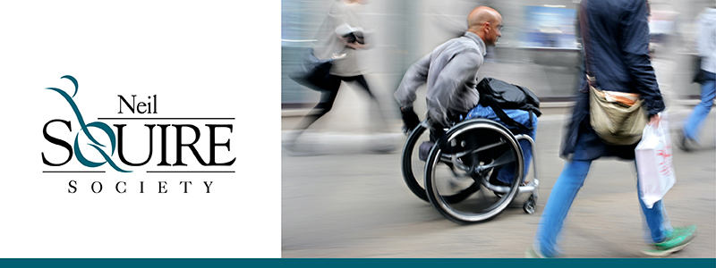 Neil Squire Society logo, image of a man in a wheelchair on a busy sidewalk
