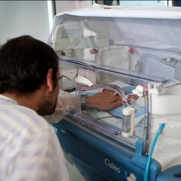 Father reaching into an incubator to touch his baby