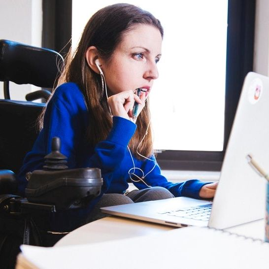 A woman wearing headphones working on a computer. She sits in a power wheelchair.