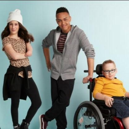Three kids. Two are standing and one is sitting in a wheelchair.
