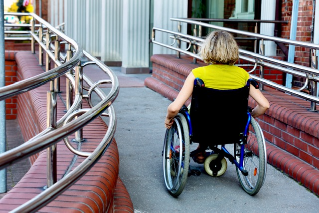 A woman pushing herself in front of a building