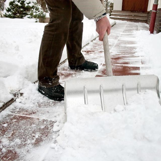A person shoveling a snowy sidewalk.