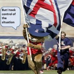Wilbur running down the football field with a UA flag