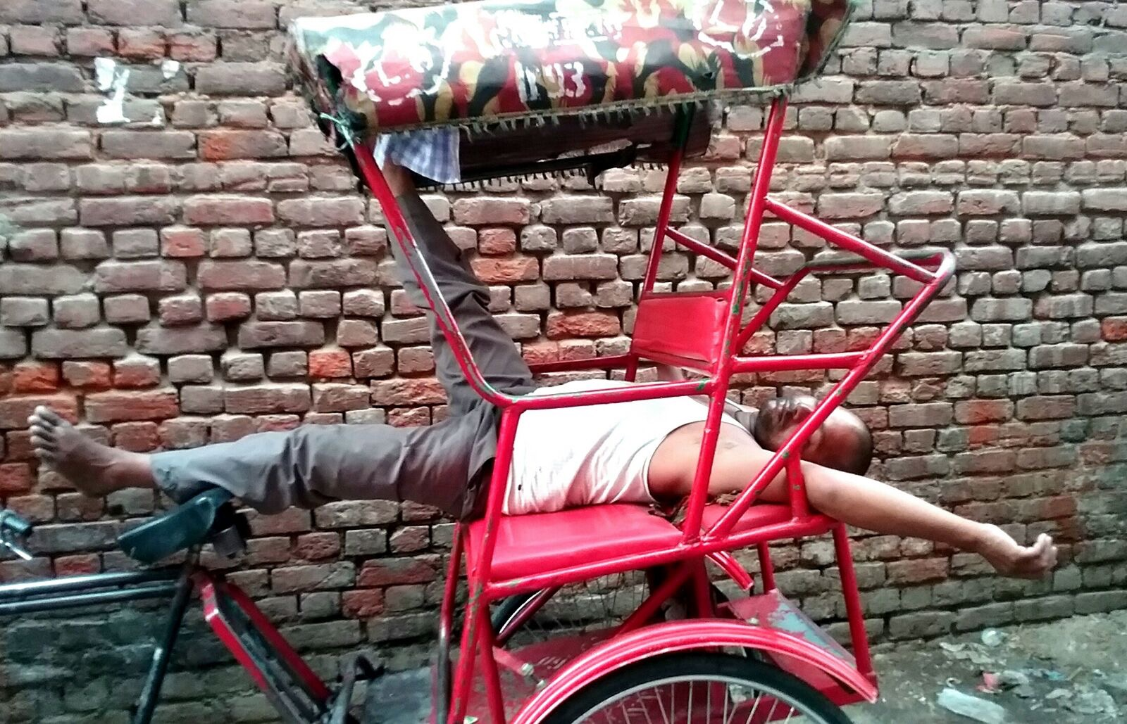 Man taking a nap on bicycle cart, Makaibari - Morning puja (blessings)