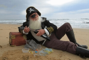Captain Trash plays uke on beach