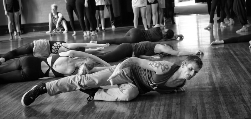 Dan Daw participating in the rolling task with students, laying on the ground, mid roll, black and white