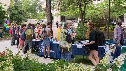 A picture of students interacting with CWRU faculty and representatives from international institutions at outdoor tables during the Study Abroad Fair