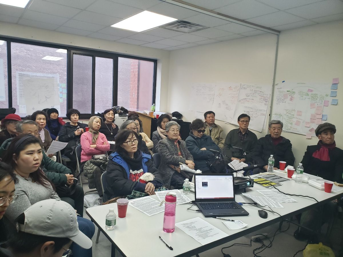 Korean low-income and senior tenants look at a presentation on housing rights.