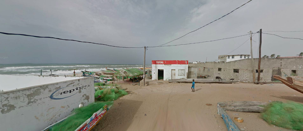 Google Earth street view image of a beachside area in Thiès, Senegal. On there is a short beach full of small fishing boats piled with green nets. Slightly futher inland there are some single storey flat roofed buildings and a sandy flat street. A small figure in blue stands in the centre. Electricity poles and wires stretch overhead and the sky looks grey and cloudy.