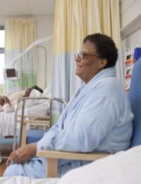 Older lady sitting in a chair in a hospital ward
