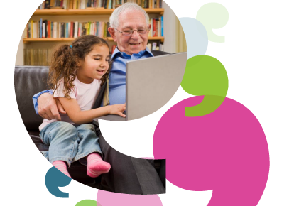 A picture of an older man sitting with his granddaughter, using a laptop