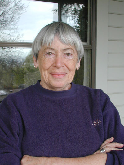 Portrait of Ursula Le Guin smiling at the camera with a wool sweater on.