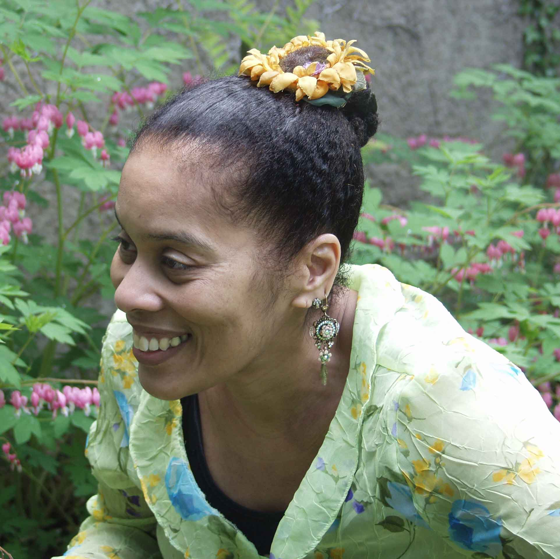 Portrait of Andrea Hairston in a flowery blouse against a leafy background