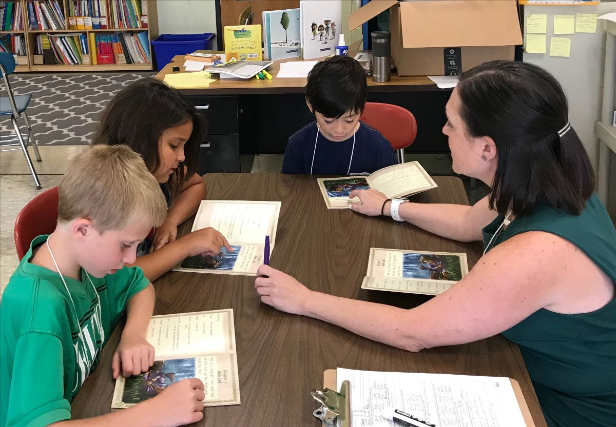 Three students and a teacher sit arond a table. They each have a copy of the same picture book and are looking at the books together.