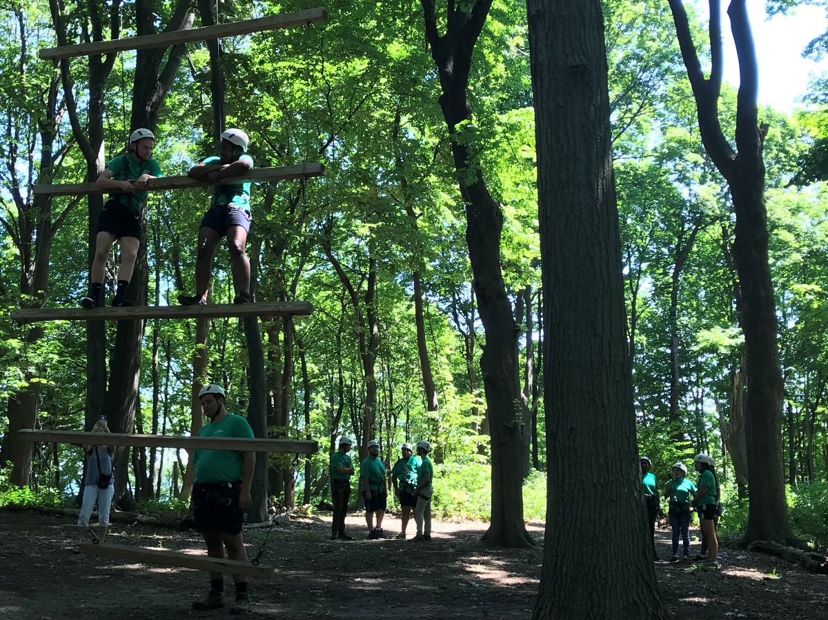 In a forest with tall trees, two students stand on a huge ladder made out of long logs and robes. They're wearing helmets and green t-shirts, and other adults and students stnad on the ground wearing the same thing. In the background, a photographer is taking a picture of the giant ladder.
