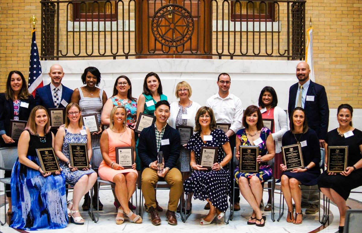 17 teachers in two rows, one seated, one standing, hold plaques or awards they received.
