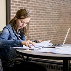 A student studies at a hallway table on the third floor of Oliver Hall.