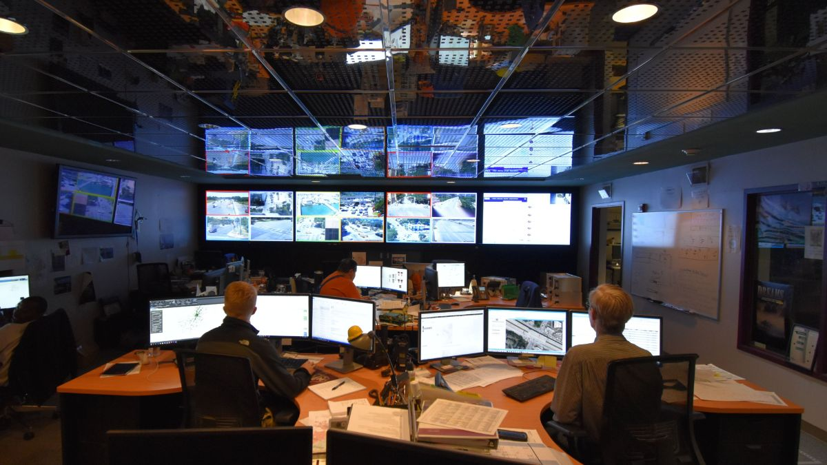 Photo of people working at Transportation Management Center, room with many computer workstations and screens showing Austin intersections.