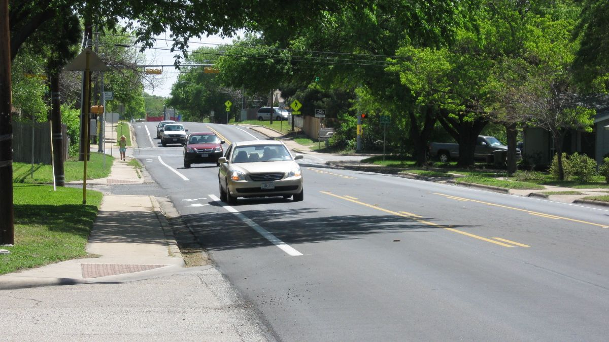 Photo of cars driving on street with sidewalks and bicycle lanes.