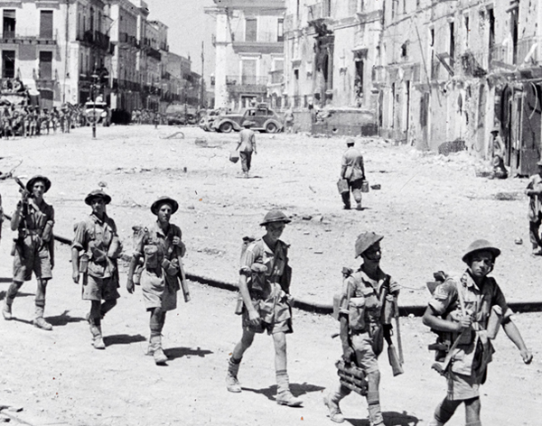 Allied soldiers marching through an Italian town in Second Word War