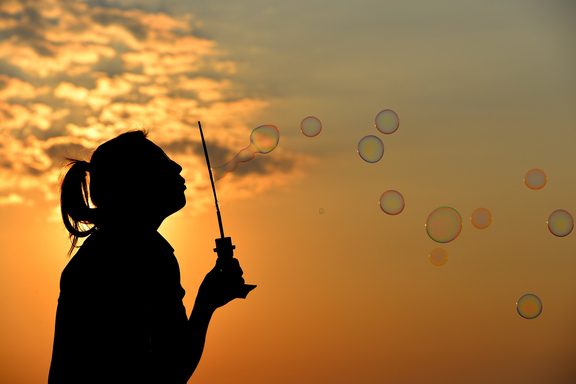 Silhouette of a woman blowing bubbles in front of sunset