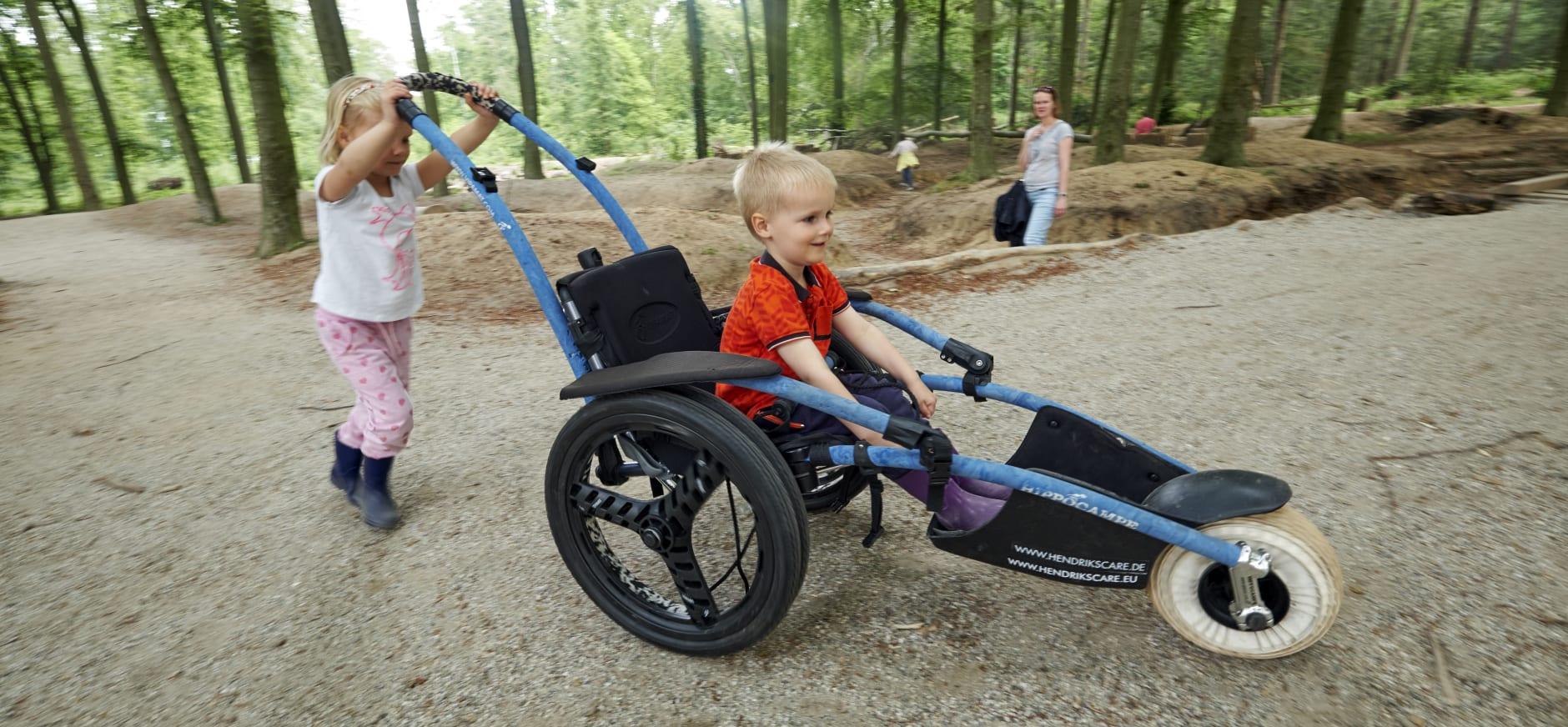 Klein meisje duwt broertje in speciale rolstoel door speelbos