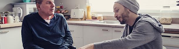 Twee mannen in keuken aan tafel, gesprek voerend