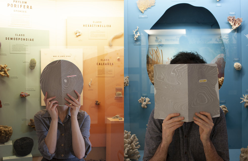 Two artists covering their faces in front of ocean artifacts
