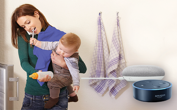 Pictured: a mother holding her toddler while retrieving a baby bottle from the fridge with an Amazon Echo and Google Home in the foreground