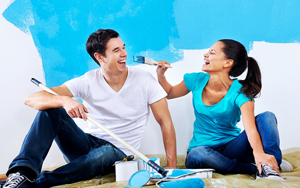 Pictured: a husband and wife paint a room as they remodel their home.