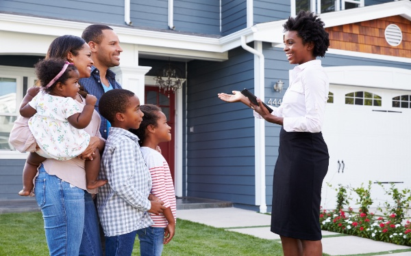 Pictured: a realtor showing a family a home that's on the market.