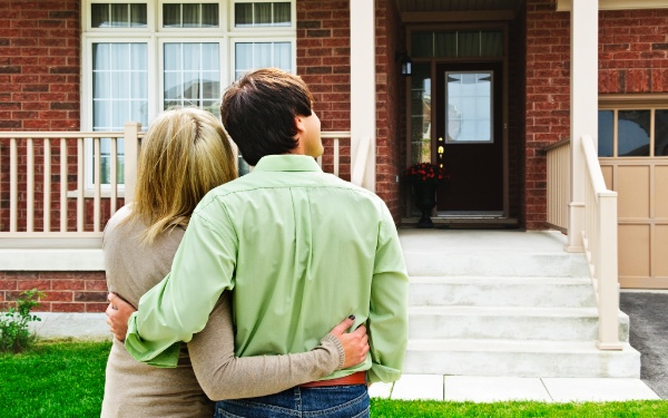 Image of couple looking at their brick home
