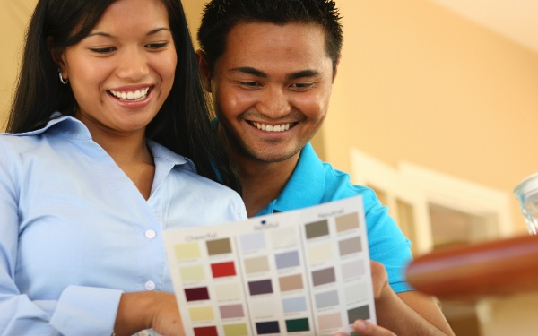 Pictured: a husband and wife choose a paint color as they remodel their home.