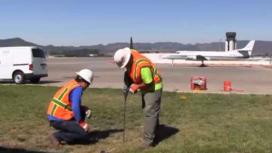 Workers insert soil-gas rod to pull sample for testing.