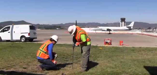 Two men conducting soil-gas sampling at County airport