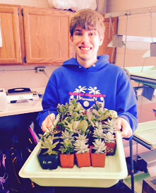 A Mt. Horeb student shows off plants potted in home-made potting soil