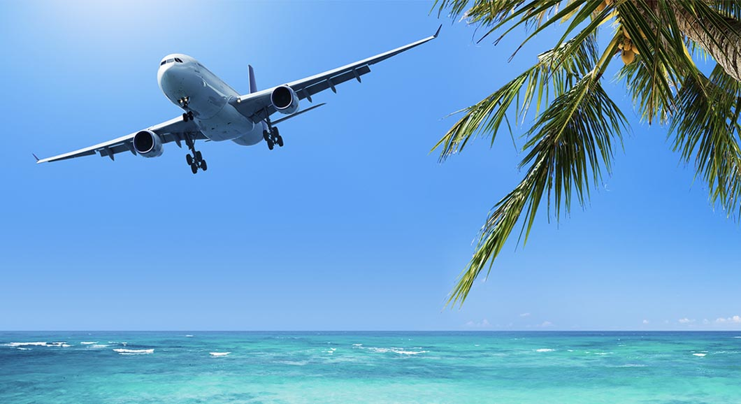 Airplane flying past tropical beach