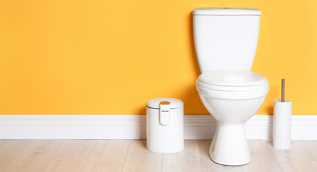 White toilet with orange wallpaper background