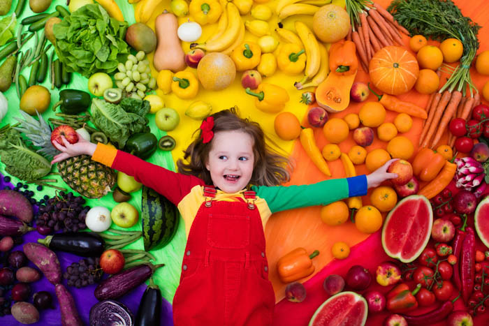 a girl surrounded by colourful fruits and vegetables