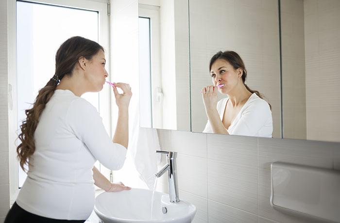 pregnant woman brushing her teeth